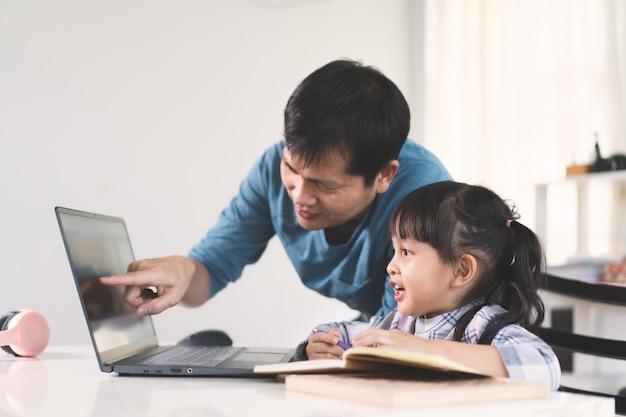 O pai asiático está ajudando e apoiando a filha a estudar a lição da aula on-line.