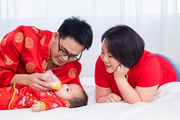 O pai asiático guarda o leite da garrafa para a cama da criança filho em casa enquanto a mãe olha para o bebê com amor, nova família traje chinês vermelho que amamenta alimentação infantil, família de estilo de vida no festival do ano novo chinês