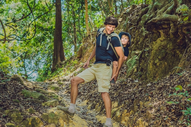 O pai carrega o filho em um bebê carregando está caminhando na floresta