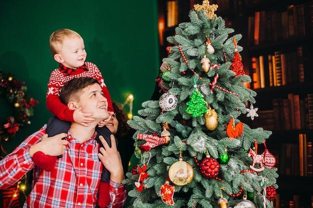 O pai coloca com seu filho pequeno no quarto vestido para o natal e ano novo