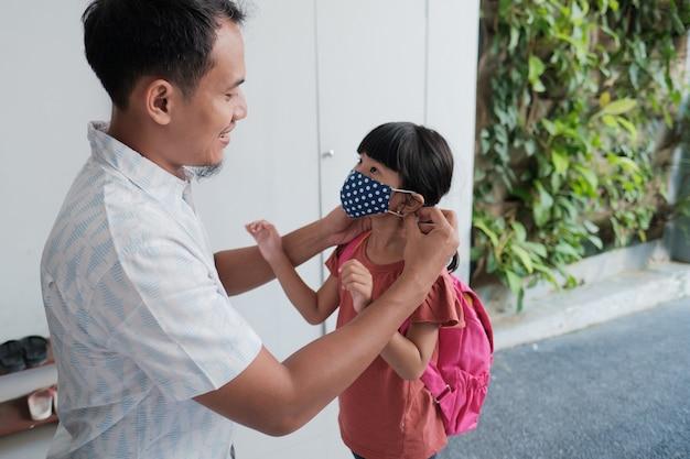 O pai colocou uma máscara na filha para proteção contra o vírus corona antes de ir para a escola