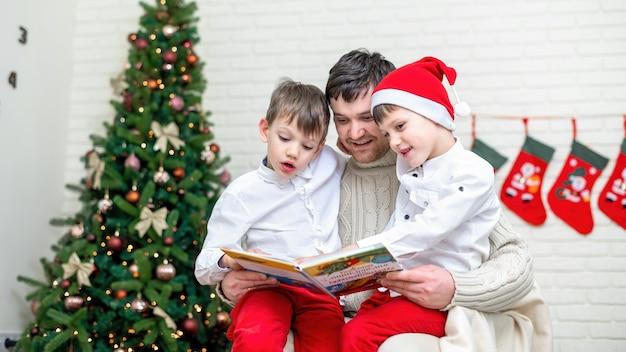 O pai com os filhos está lendo um livro perto da árvore de natal em casa. ideia de família feliz
