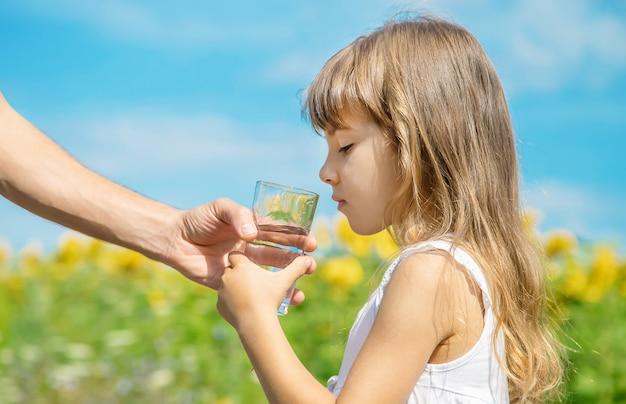 O pai dá à criança água no fundo do campo