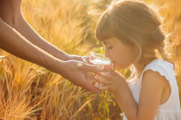 O pai dá à criança um copo de água. foco seletivo.