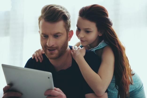 O pai de cabelo vermelho e a filha adolescente estão olhando.