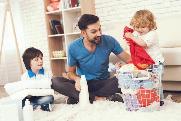 O pai do sorriso está ensinando a uma limpeza dos filhos.