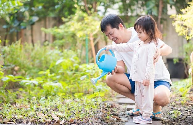 O pai e a filha asiáticos estão molhando o jardim de vegetais em casa.