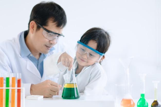 O pai e a filha asiáticos fazem um experimento sobre a separação de fases de óleo e água.