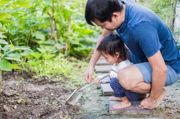 O pai e a filha asiáticos no verduras pequenas jardinam em casa.