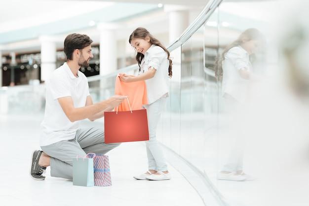 O pai e a filha compraram a camisola nova no shopping.
