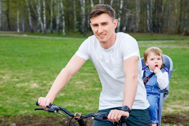 O pai e a filha montam uma bicicleta no parque.