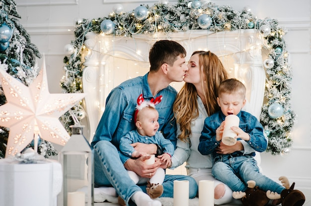O pai e a mãe abraçam o filho e a filha perto da árvore de natal