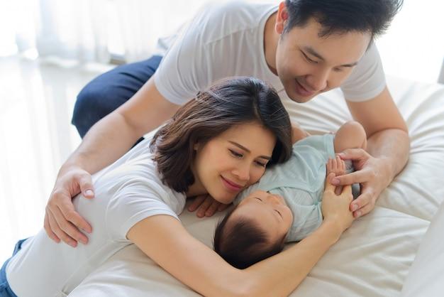 O pai e a mãe asiáticos estão abraçando o bebê recém-nascido novo no sofá.