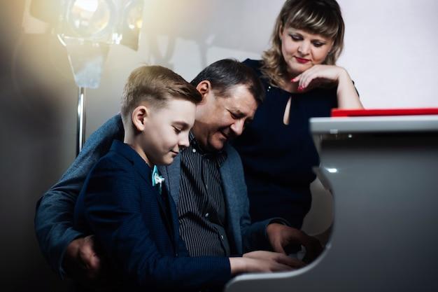 O pai e a mãe ensinam o filho a tocar um instrumento musical