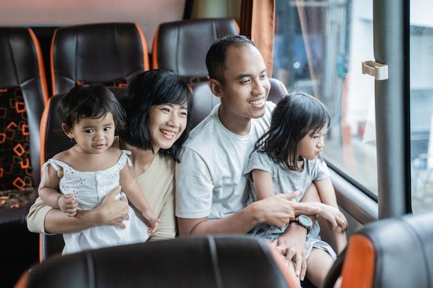 O pai e a mãe seguraram seus dois filhos sentados no banco do ônibus durante a viagem