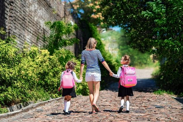 O pai e dois alunos da escola primária andam de mãos dadas. mulher e meninas com mochila nas costas. início das aulas. primeiro dia de outono