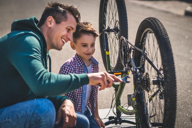 O pai e filho consertando a bicicleta