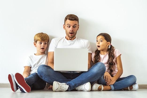 O pai e filhos surpresos com um laptop sentado no chão