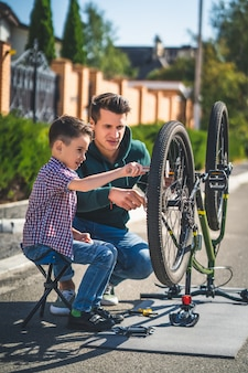 O pai e o filho consertam a bicicleta ao ar livre