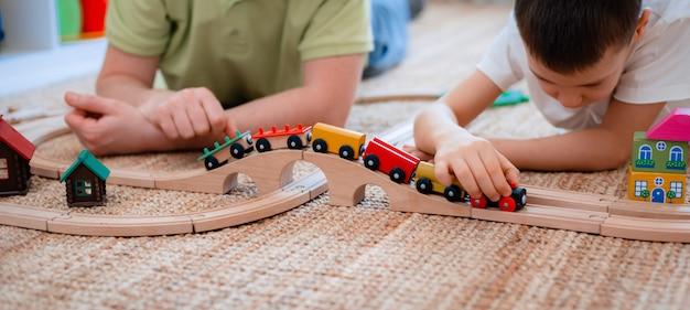 O pai e o filho da família jogam a estrada de ferro de madeira do brinquedo na sala de jogos. o conceito de um filho pai passar um tempo juntos