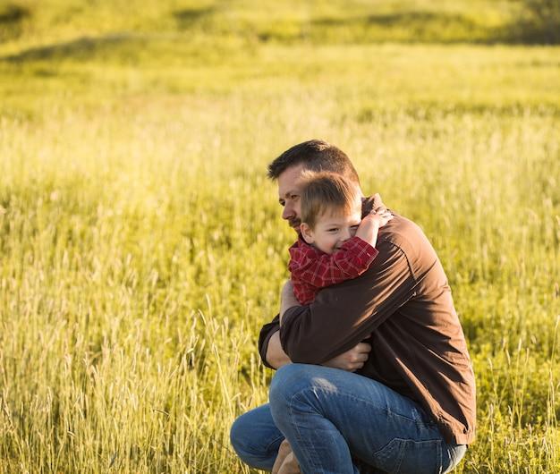 O pai e o filho novos de sorriso abraçam o relaxamento no prado. feliz pai e filho descansem no campo de grama-pena