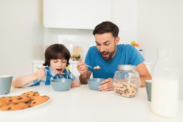 O pai e o filho tomam o café da manhã na cozinha clara.