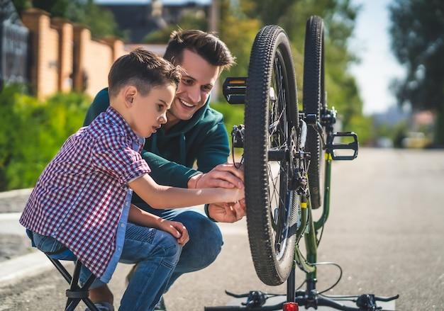 O pai e o filho verificando a corrente da bicicleta