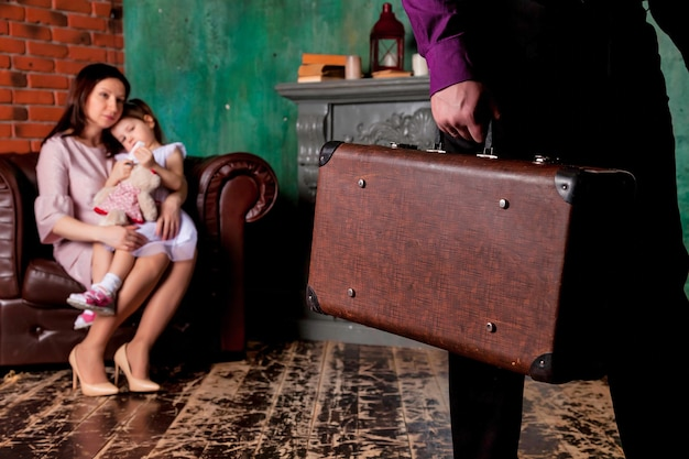 O pai e o marido do homem adulto deixam a família com a mala. problemas de conceito na família, orfandade e maternidade solteira. mãe e filha tristes na cadeira da sala cuidando da partida do pai