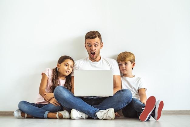 O pai e os filhos com um laptop sentado no chão