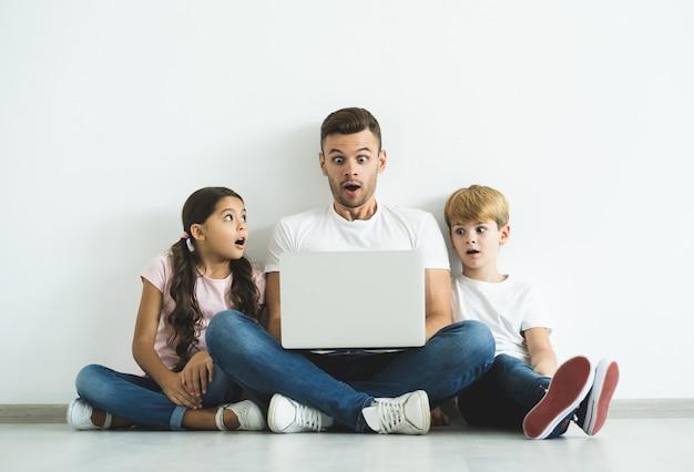 O pai e os filhos surpresos com um laptop sentado no chão