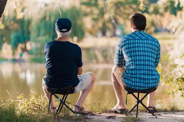 O pai e seu filho adulto estão pescando juntos