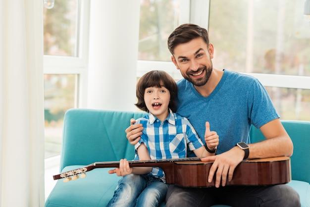 O pai ensina seu filho a tocar violão.