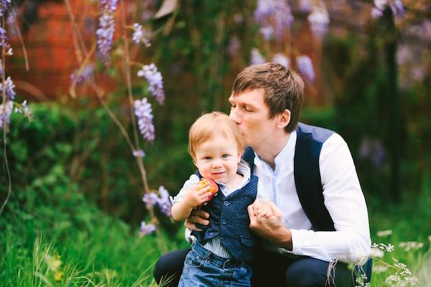 O pai está beijando o filho enquanto dá um passeio no parque