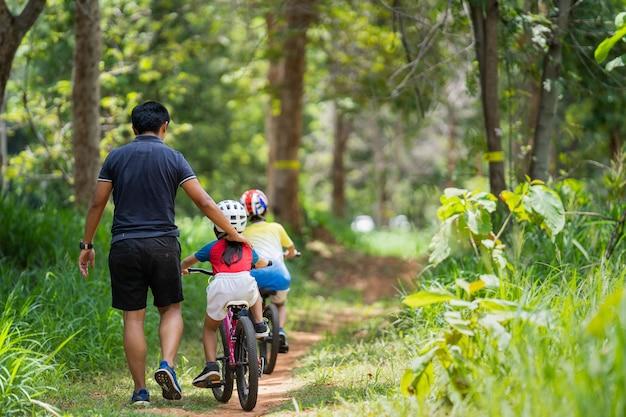 O pai está levando os filhos para praticar ciclismo.