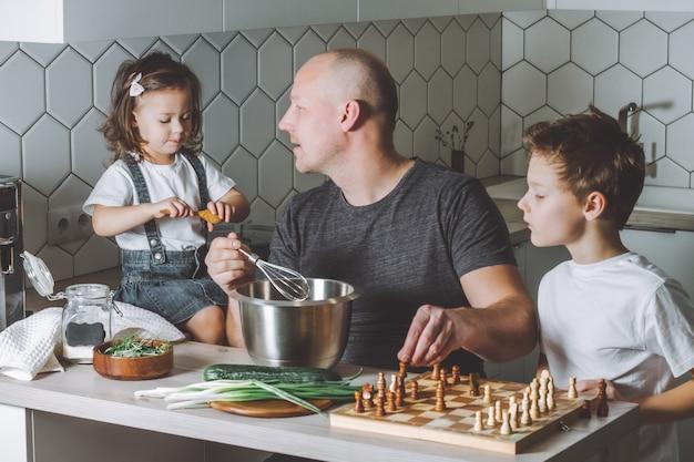 O pai faz uma omelete com um batedor jogando xadrez com o filho e conversando com a filha fazendo tarefas