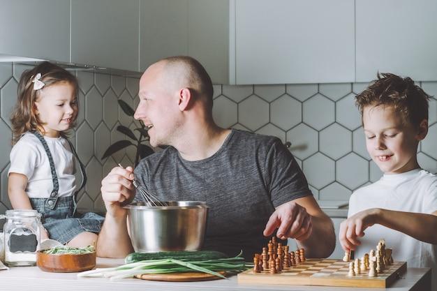 O pai faz uma omelete com um batedor