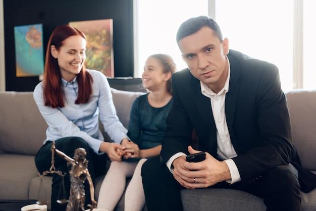 O pai frustrante com o telefone nas mãos senta-se no sofá.