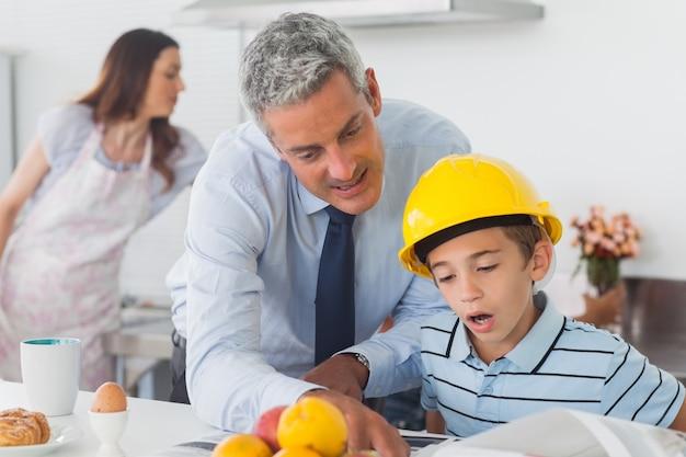 O pai mostrando o filho seus planos como ele está usando o capacete de segurança