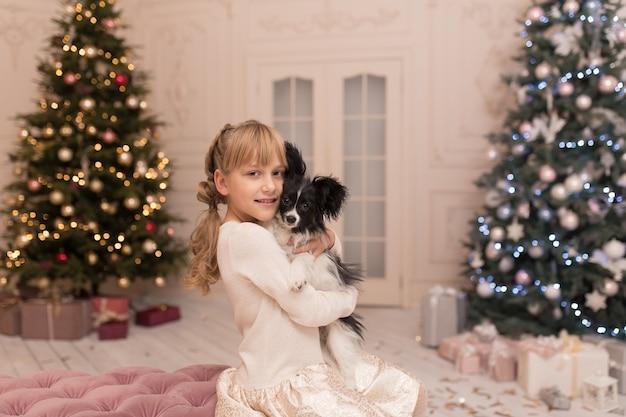 O pai natal deu à rapariga um cão de natal. conto de natal. infância feliz. primeiro animal de estimação.