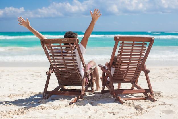 O pai novo com a filha nas cadeiras de praia levantou suas mãos acima do oceano da costa