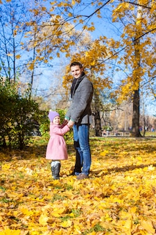 O pai novo e a menina apreciam férias no parque do outono