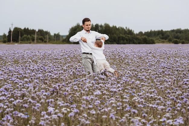 O pai pegou o filho nos braços e brincou com ele em um campo florido