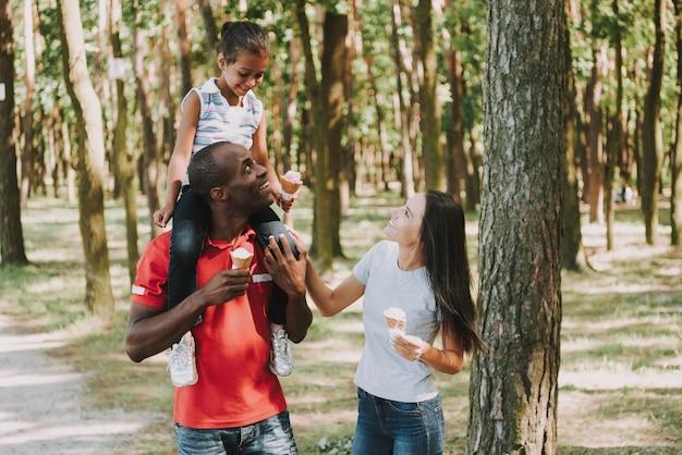 O pai preto leva a filha no pescoço na floresta.