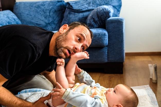 O pai que esforça-se com sua filha do bebê para mudar as fraldas sujas que colocam as faces do esforço, conceito da paternidade.