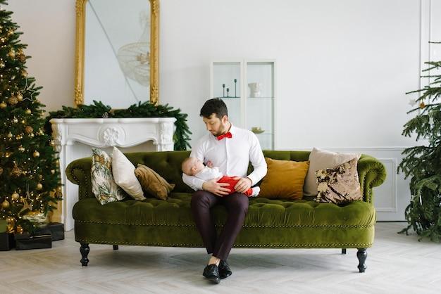 O pai se senta no sofá e segura o filho na sala perto da lareira e da árvore de natal