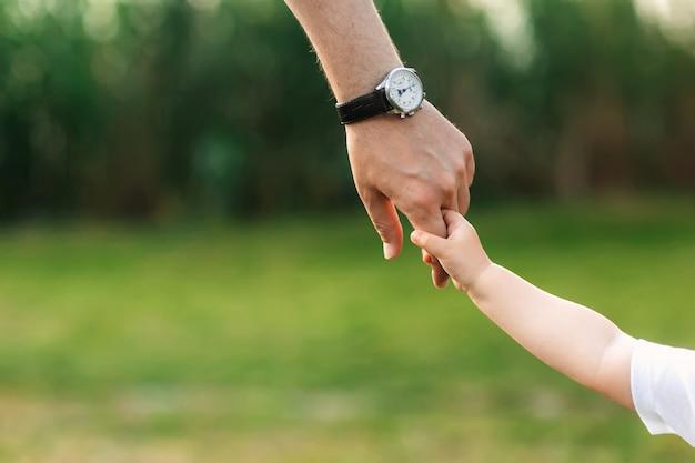 O pai segura a criança pela mão