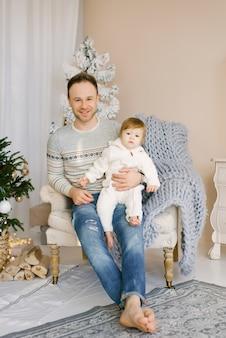 O pai segura a filha nos braços e se senta em uma cadeira perto da árvore de natal