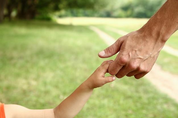 O pai segura a mão de uma criança pequena
