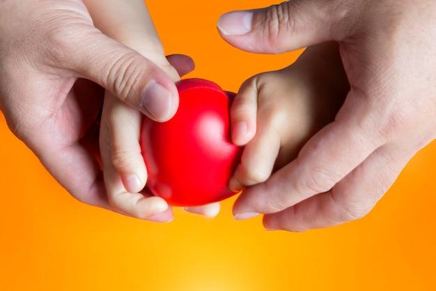O pai segura a mão do miúdo no fundo laranja