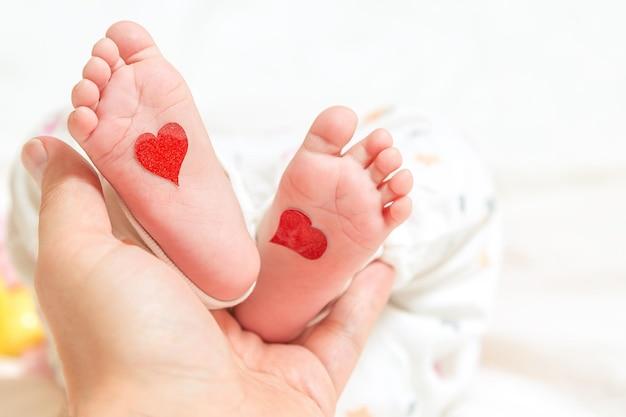 O pai segura uma pequena perna de um coração de bebê recém-nascido para o dia dos pais ou dia dos namorados